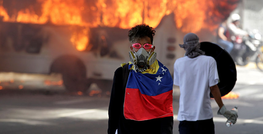 Demonstrators stand next to a bus burns near a protest against Venezuela's President Nicolas Maduro's government in Caracas, Venezuela, May 13, 2017.
