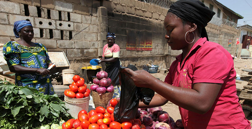A woman sells tomatoes at a roadside grocery stall in Nigeria's central city of Jos