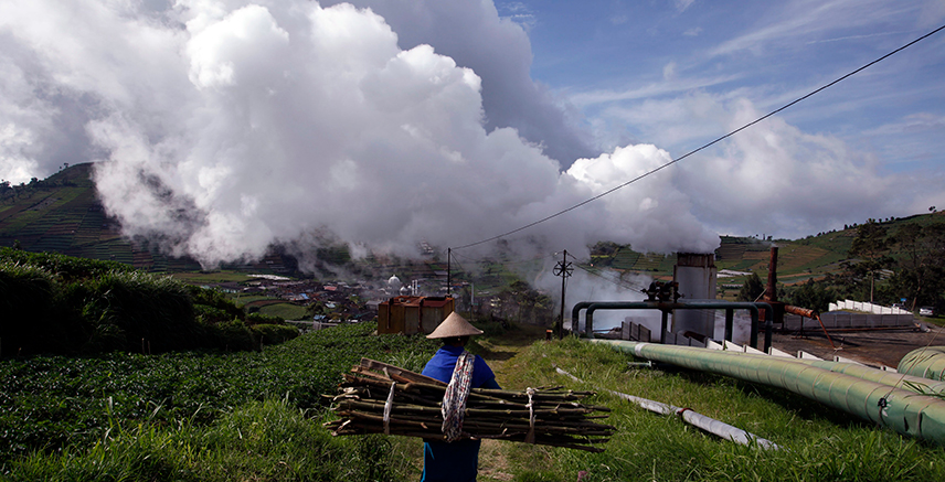 A villager carrying wood for cooking walks near Dipa Energi's Geothermal Power Plant (PLTP) project at Dieng mountain area, Central Java province October 3, 2010. REUTERS