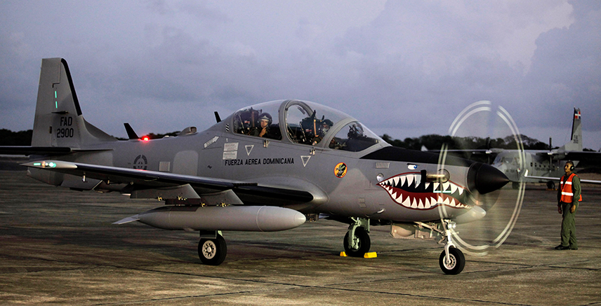 Military officers arrive in a combat plane, known as a Super Tucano, during a ceremony at a military base in Santo Domingo December 10, 2009. The Brazilian aircraft were purchased to combat drug trafficking in the Caribbean island, local media reported. REUTERS/ Eduardo Munoz