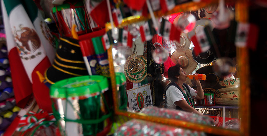 A woman drinking a soft drink is seen reflected in a mirror in a souvenir shop in Mexico City