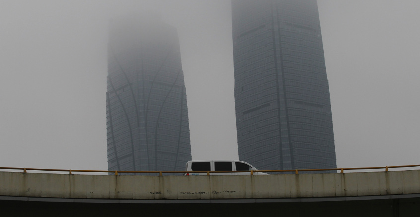 A minivan drives past skyscrapers in Kunming, Southern China. Eastern Thailand is set to be connected with Kunming as part of the One Belt, One Road initiative.